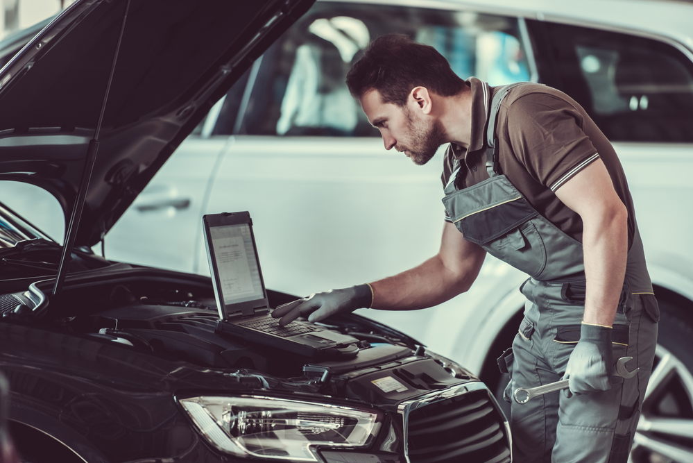 mechanic is using a laptop while repairing car in auto service